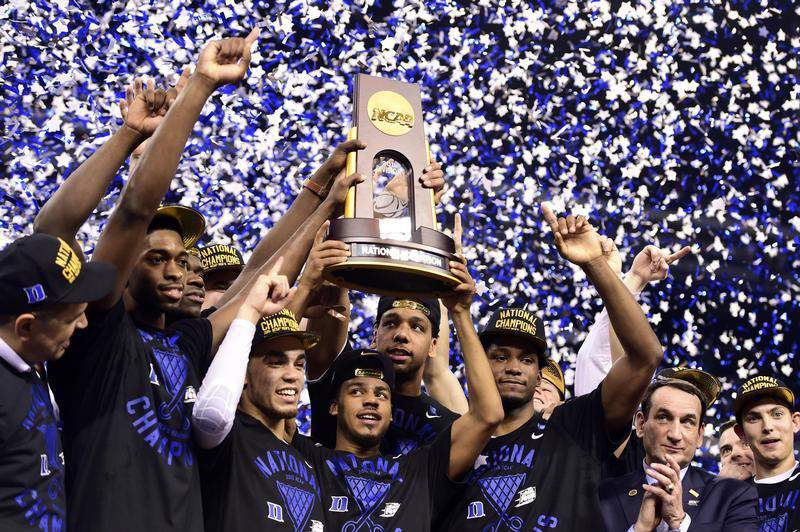 Apr 6, 2015; Indianapolis, IN, USA; Duke Blue Devils guard Quinn Cook (middle) and teammates hoist the NCAA championship trophy after defeating the Wisconsin Badgers in the 2015 NCAA Men's Division I Championship game at Lucas Oil Stadium. Mandatory Credit: Bob Donnan-USA TODAY Sports - RTR4WB65